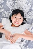 stock photo of laying-in-bed  - little girl laying on in bed with hands gesture - JPG