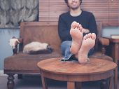 stock photo of barefoot  - A barefoot young man is resting his legs on a coffee table at home there is a cat on the sofa next to him - JPG