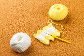 image of knitting  - roll of white and yellow soft knitting yarn knitting needle on cork background - JPG