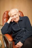 stock photo of recliner  - portrait of a smiling old man with a head reclined upon his hand - JPG