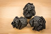 image of stress-ball  - Black paper ball corrugate on wooden background - JPG