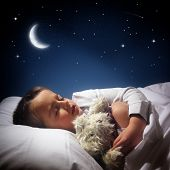 stock photo of moon stars  - Child sleeping and dreaming in his bed under the moon - JPG