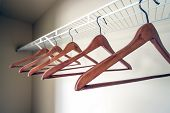 picture of clothes hanger  - Coat hangers on a clothes rail in an empty closet - JPG