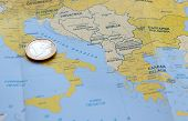 pic of crisis  - One Euro coin resting on Italy on a European map - JPG