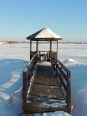 image of gazebo  - Wooden gazebo and planked footway by the river at winter - JPG