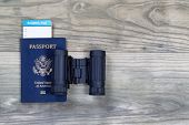 image of boarding pass  - United States passport boarding pass and binoculars on faded wooden boards - JPG
