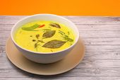 image of curry chicken  - Hot and spicy chicken green curry on a yellow background on a wood table top - JPG
