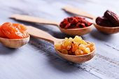 foto of dry fruit  - Dried fruits in spoons on color wooden table background - JPG