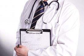 stock photo of hospital patient  - Male doctor fills patient registration form prior to admission and examination - JPG