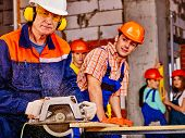 pic of millwright  - Happy group people  and old man builder with circular saw - JPG