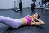 stock photo of crunch  - Muscular woman doing abdominal crunch at the crossfit gym - JPG