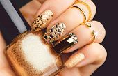 Golden Nail art manicure. Holiday style bright Manicure with gems and sparkles. Bottle of Nail Polis poster