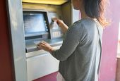 finance, money, bank and people concept - close up of woman inserting card to atm machine poster