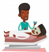 African cosmetologist applying cosmetic mask on face of client in beauty salon. Young man lying on t poster