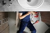 Male plumber repairing sink pipes in kitchen, top view poster