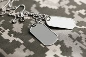 Army tokens on military uniform background poster
