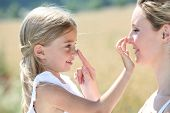 stock photo of sunburn  - Mother and daughter putting sunscreen on their face - JPG