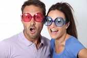 image of lottery winners  - Couple wearing colored glasses having fun on white background - JPG