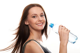 stock photo of drinking water  - Beautiful girl drinking water from blue bottle on blue background - JPG