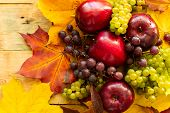 Top View On Red Juicy Ripe Apples With Grapes And Autumn Maple Leaves On A Wooden Background poster