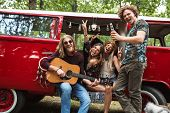 Group of hippies happy men and women laughing and playing guitar near vintage minivan into the natur poster
