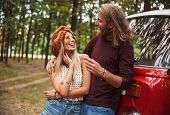 Young hippy couple man and woman smiling and hugging each other while standing near minivan in fores poster