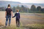 Back View Of Young Father And Son Walking Together Holding Hands By Grassy Field On Blurred Foggy Gr poster