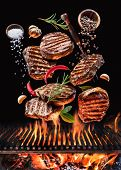 Grilled beef steaks with vegetables and spices fly over the blazing grill barbecue fire. Concept of  poster