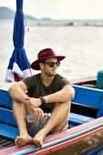 Tanned Man With Stubble Is Sailing On Colorful Boat poster