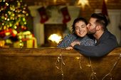 Christmas couple at home in Winter. Happy young couple kissing at home in Christmas time. Christmas  poster