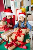 Two pretty little girls in Santa caps preparing packed giftboxes for Christmas day poster