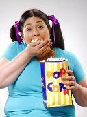 stock photo of fat woman  - Fat young woman eating popcorn - JPG