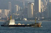 stock photo of urbanisation  - A bulk carrier ship on the waterway passing skyscrapers of Hong Kong Island Hong Kong - JPG