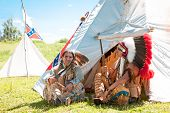stock photo of wigwams  - North American Indians sit at a wigwam - JPG