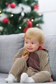 stock photo of scared baby  - Scared baby in Christmas deer suit with cookie sitting on sofa near Christmas tree