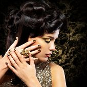 stock photo of minx  - Beautiful woman with golden nails and fashion hairstyle over creative background - JPG