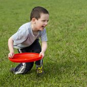 picture of frisbee  - Child boy playing on a grass with a red frisbee disk - JPG
