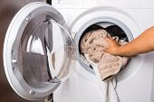 stock photo of laundromat  - Hand loading laundry to the washing machine - JPG