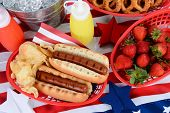 Looking down on a picnic table decorated for the 4th of July. Hot Dogs, chips, strawberries, mustard