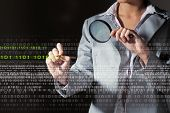 stock photo of maliciousness  - Businesswoman with magnifier glass examining binary code - JPG