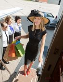 Full length portrait of confident rich woman carrying shopping bags while boarding private jet with
