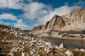 stock photo of brighten  - The clouds clear out after a storm passed through and the sun brightens the alpine country in the Medicine Bow Mountains of Wyoming - JPG