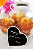 a continental breakfast with muffins, coffee and juice and the sentence happy valentines day written