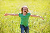stock photo of natural blonde  - Blond kid girl happy running open hands smiling in outdoor green meadow - JPG