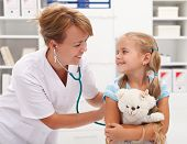 Happy little girl at the doctor for a checkup - being examined with a stethoscope