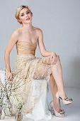 Beautiful young bride in tight gold minidress sitting on studio background