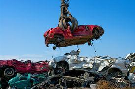 picture of scrap-iron  - Crane picking up a car in a junkyard - JPG