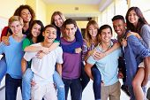 stock photo of 16 year old  - Group Of High School Students Giving Piggybacks In Corridor - JPG
