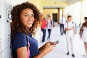 stock photo of 16 year old  - Female High School Student By Lockers Using Mobile Phone - JPG