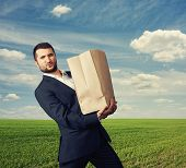 stock photo of heavy bag  - handsome man holding heavy paper bag at outdoor - JPG